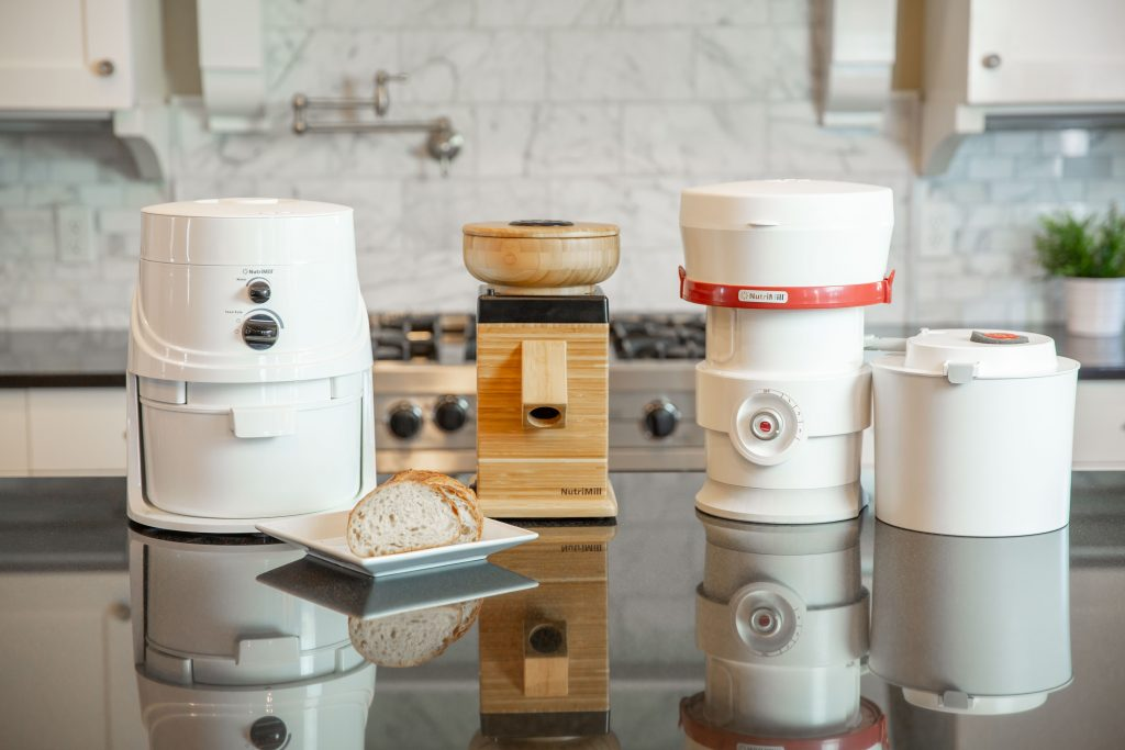 three grain mills on a kitchen counter.