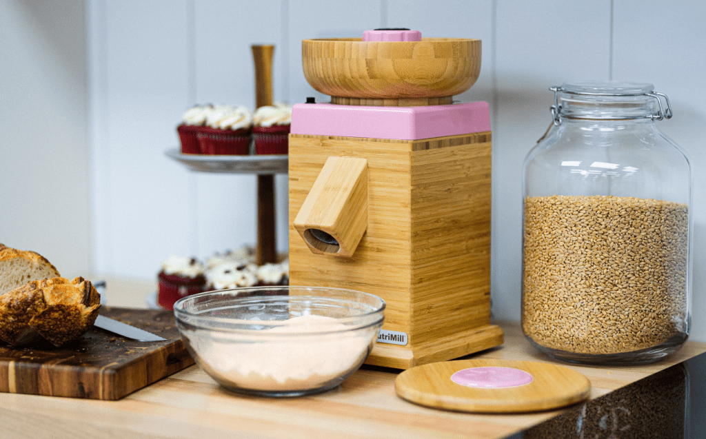 NutrtiMill Pink harvest grain mill with fresh ground flour and wholewheat